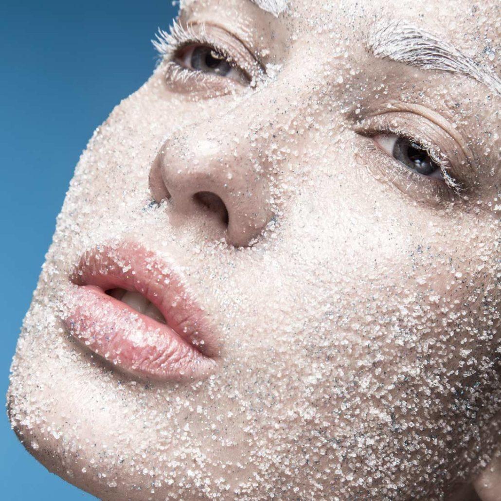 Das Bild zeigt das Gesicht einer jungen Frau, das mit Zucker bestreut ist. Zucker lässt den Körper altern.