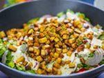 Ein Veganer Tofusalat mit frischen Zutaten auf dem Teller.